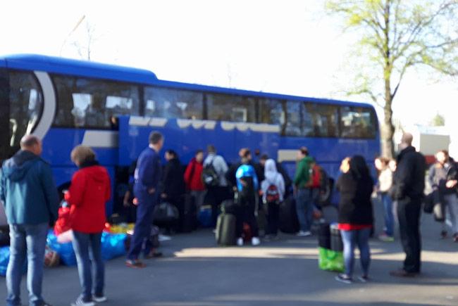 Blauer Turnierbus mit Jugendlichen, die ihre Tasche einräumen